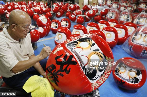 A craftsman paints a Japanese traditional daruma doll featuring the word hissho on its body in Takasaki Japan on Sept 27 as making of the doll a...