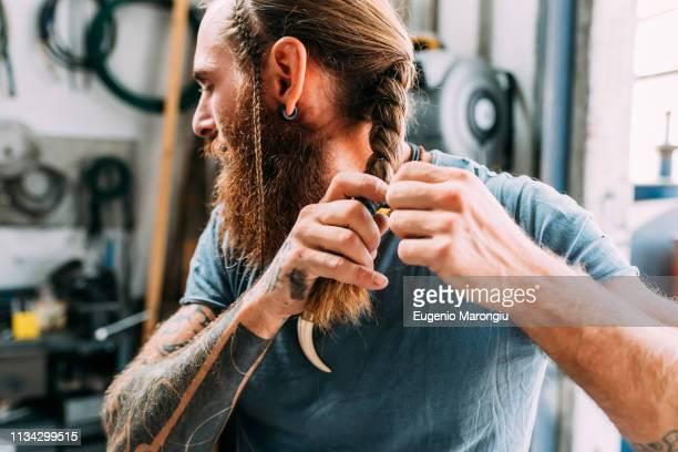 craftsman plaiting his hair in workshop - coiffure homme photos et images de collection