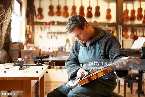 craftsman polishing violin in repair workshop - instrument maker stock photos and pictures