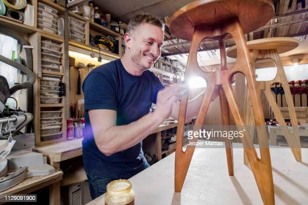 craftsman polishing wooden stool with oil finish - designer einrichtung stock-fotos und bilder