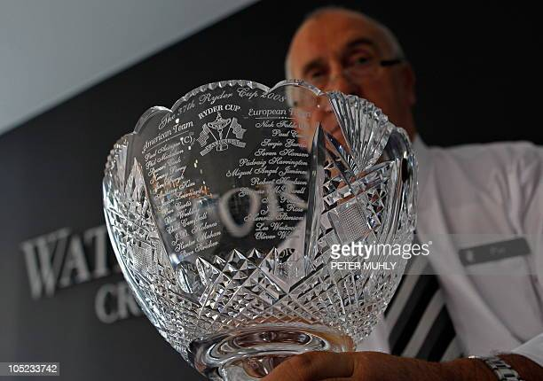 A craftsman poses for the photographer with a duplicate of the 37th Ryder Cup Waterford crystal bowl which was presented to the players in Valhalla...