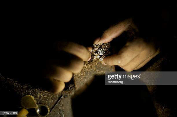 A craftsman puts diamonds into a gold pendant at a diamond finishing and jewelry workshop in Mumbai India on Tuesday Nov 10 2009 Rough diamonds are...