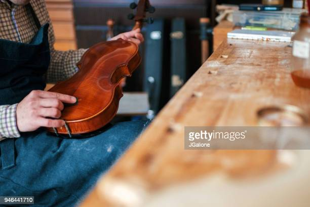 Craftsman repairing a blemish on an antique violin