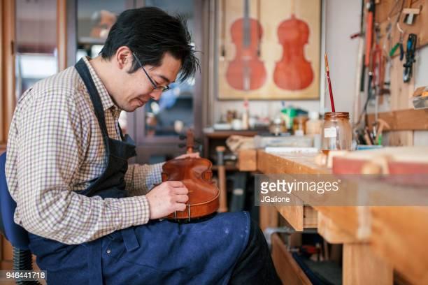 Craftsman repairing a blemish on an antique violin