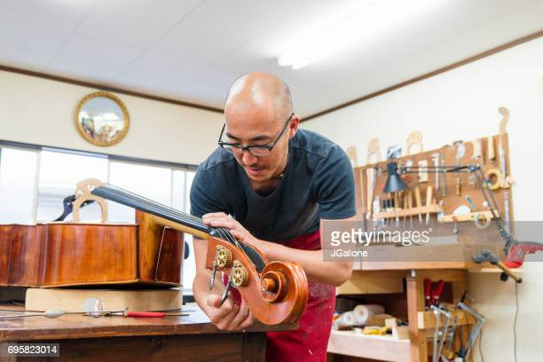 craftsman repairing a double bass in his workshop - bassoon stock pictures, royalty-free photos & images