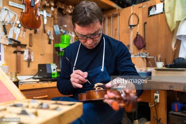 Craftsman repairing an antique violin