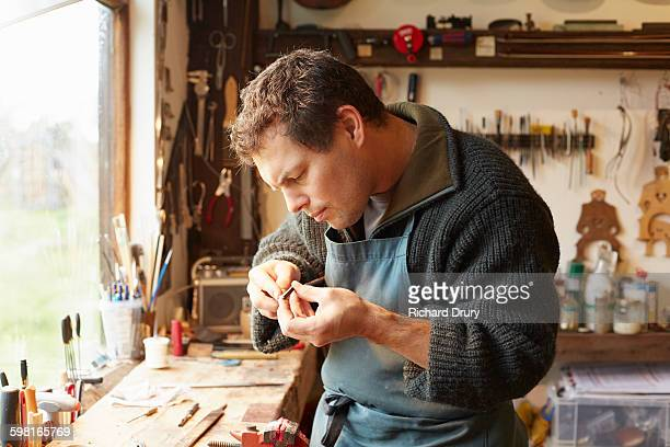craftsman repairing bow in violin workshop - richard drury stock pictures, royalty-free photos & images