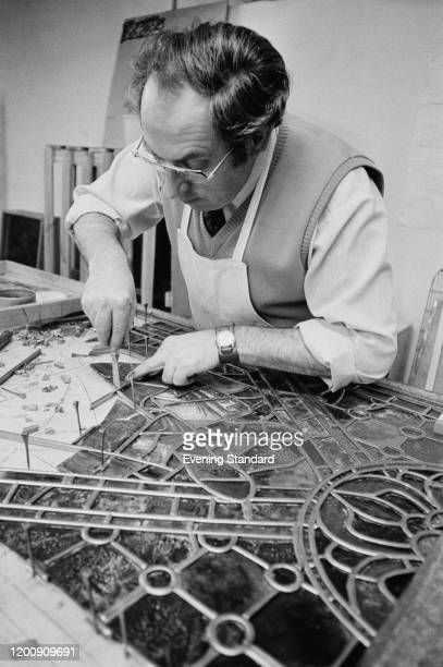 A craftsman repairing stained glass at Canterbury Cathedral in Canterbury Kent England February 1976