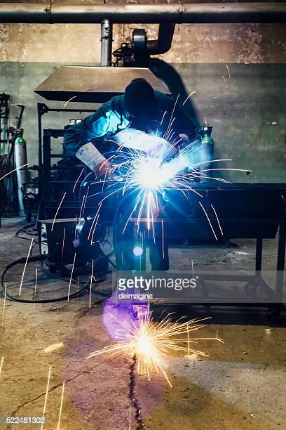 Craftsman repairman is working with welding machine torch
