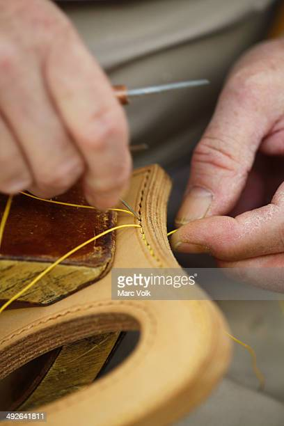 Craftsman sewing leather, close-up of hands