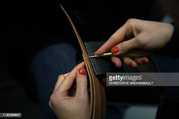 A craftsman stitches pieces of leather as part of a saddle at the French luxury brand Hermes' saddlery in Paris on March 11 2019 Since 1880 Hermes...