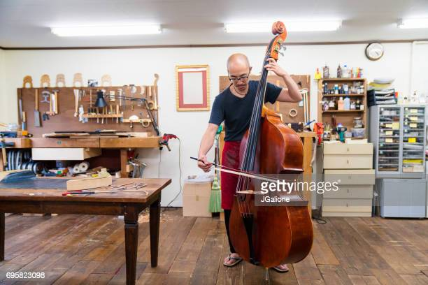 craftsman testing a double bass in his workshop - bassoon stock pictures, royalty-free photos & images