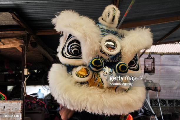A craftsman try the Barongsai head costume at home industry costume maker in Bogor Indonesia on February 9 2018 The Liong and Barongsai dance will...