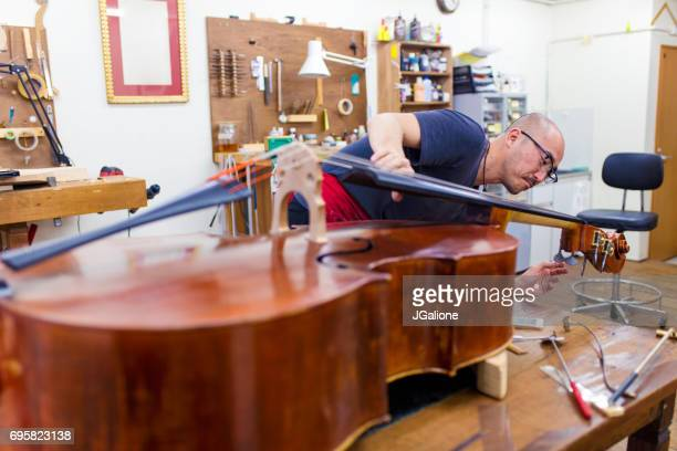 craftsman tuning a double bass in his workshop - bassoon stock pictures, royalty-free photos & images