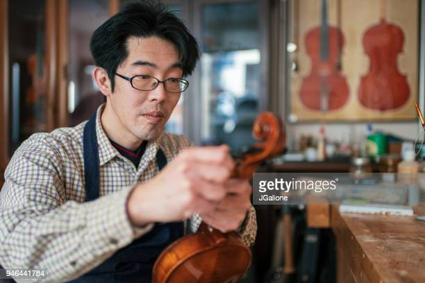 Craftsman tuning a violin