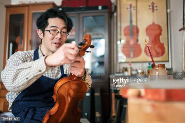 Craftsman tuning a violin