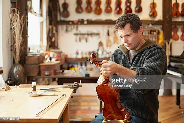 craftsman tuning violin in repair workshop - instrument maker stock photos and pictures