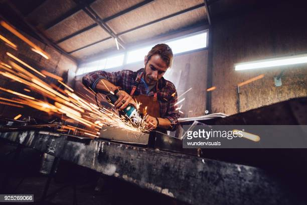 Craftsman using angle grinder and cutting metal in blacksmith shop