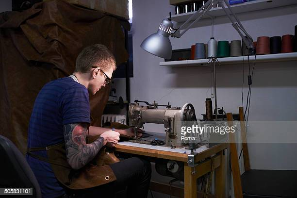Craftsman using sewing machine to stitch leather
