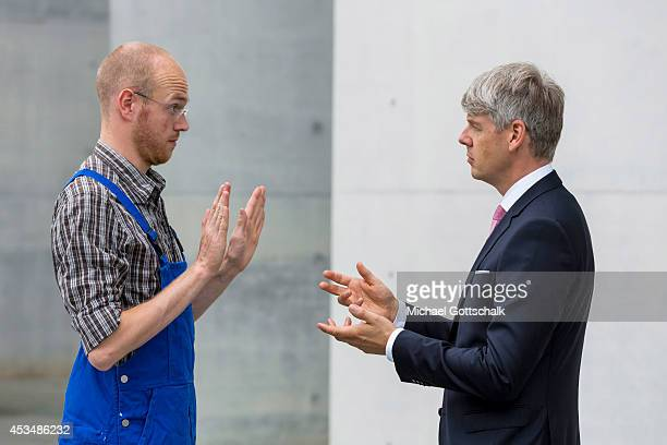 A craftsman wearing a boiler suit and a man wearing a business suit gestues during an argument on August 07 2014 in Berlin Germany