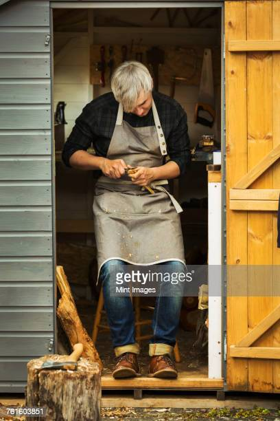A craftsman wearing a hessian apron sitting in the doorway of a workshop, carving a small piece of wood.