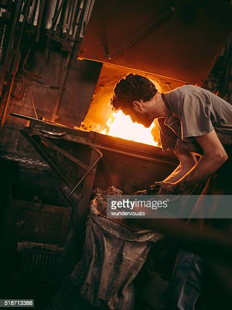 Craftsman working furnace in blacksmith's shop