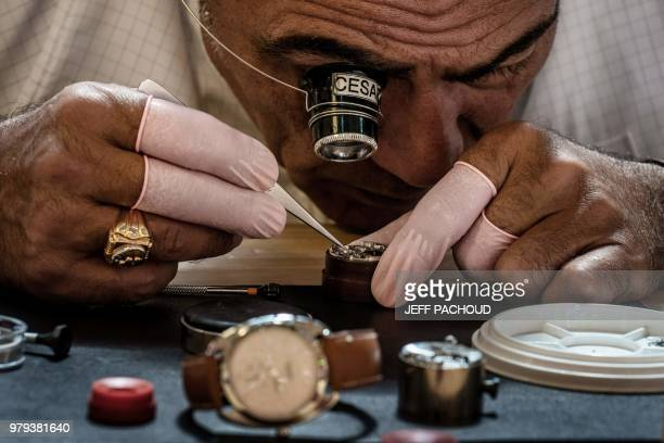 A craftsman works on watch on June 20 at the Palais de la Bourse in Lyon during the Hermes Hors les Murs event where French fashion luxury goods...