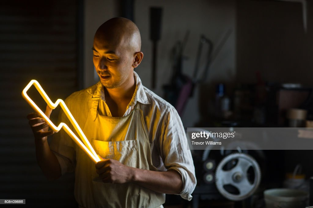 Craftsmen holding a lightning bolt shaped neon light : Stock Photo