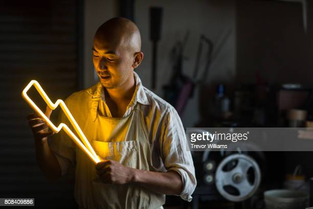 craftsmen holding a lightning bolt shaped neon light - craftsman stock photos and pictures
