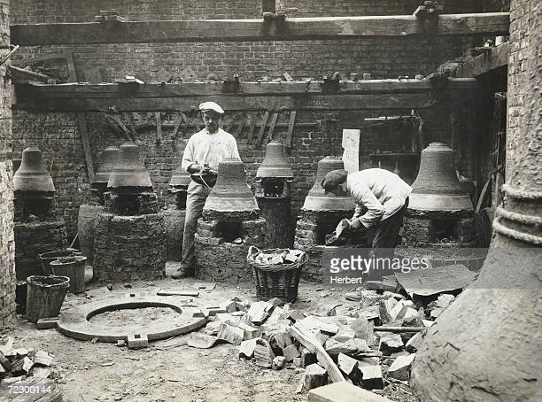 Craftsmen in France making bells circa 1900 The man on the left is measuring the bell mold while the other sets the fire in one of the brick kilns