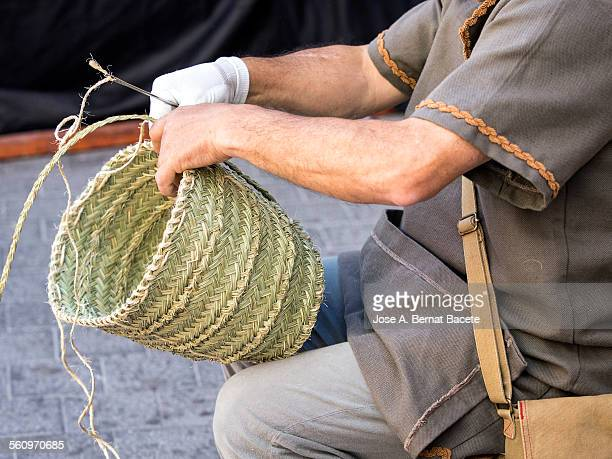Craftsmen making up a basket of straw
