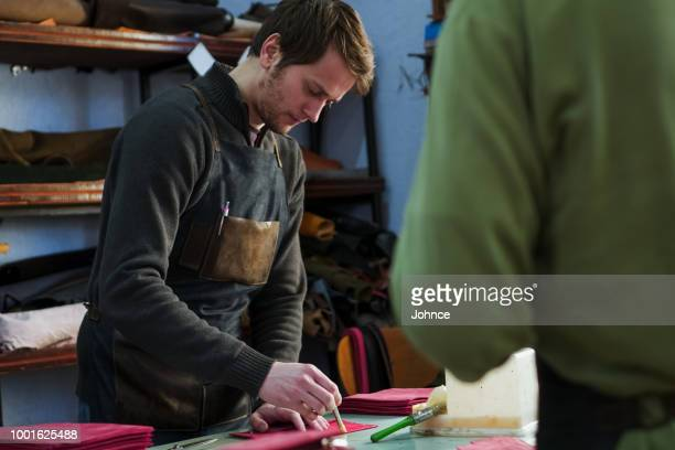 craftsmen prepares leather product for binding - cowhide stock photos and pictures