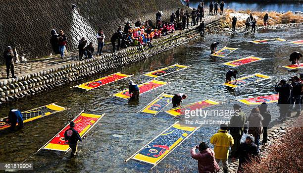 Craftsmen remove starch glue as a part of process of producing carp streamers at Kodara River on January 20, 2015 in Gujo, Gifu, Japan. The carp...