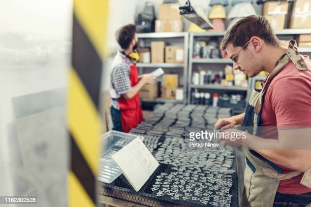 craftsmen reviewing metal component at the warehouse - spare part stock pictures, royalty-free photos & images