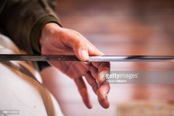 a craftsmen sharpens a traditional japanese sword - sword stock pictures, royalty-free photos & images