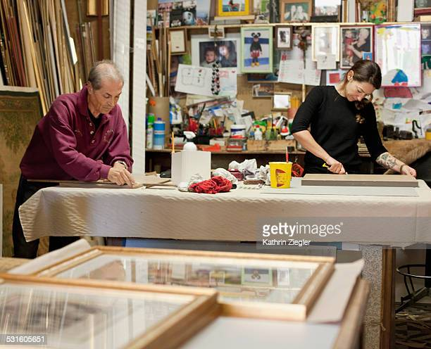 craftspeople working in frame shop