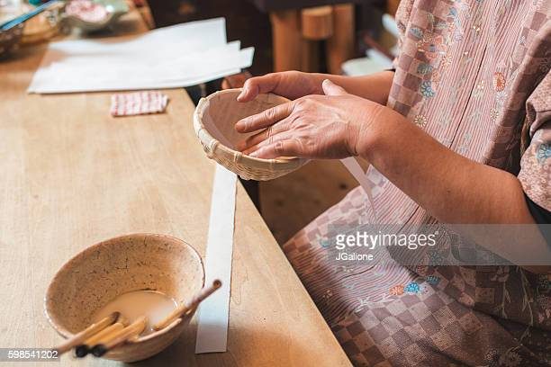 Craftsperson adding strips of paper to a handmade bowl