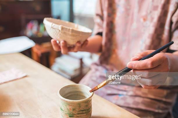 Craftsperson handpainting a paper bowl