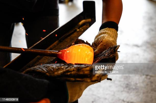 craftsperson holding blowpipe with molten glass at workshop - blowpipe stock pictures, royalty-free photos & images
