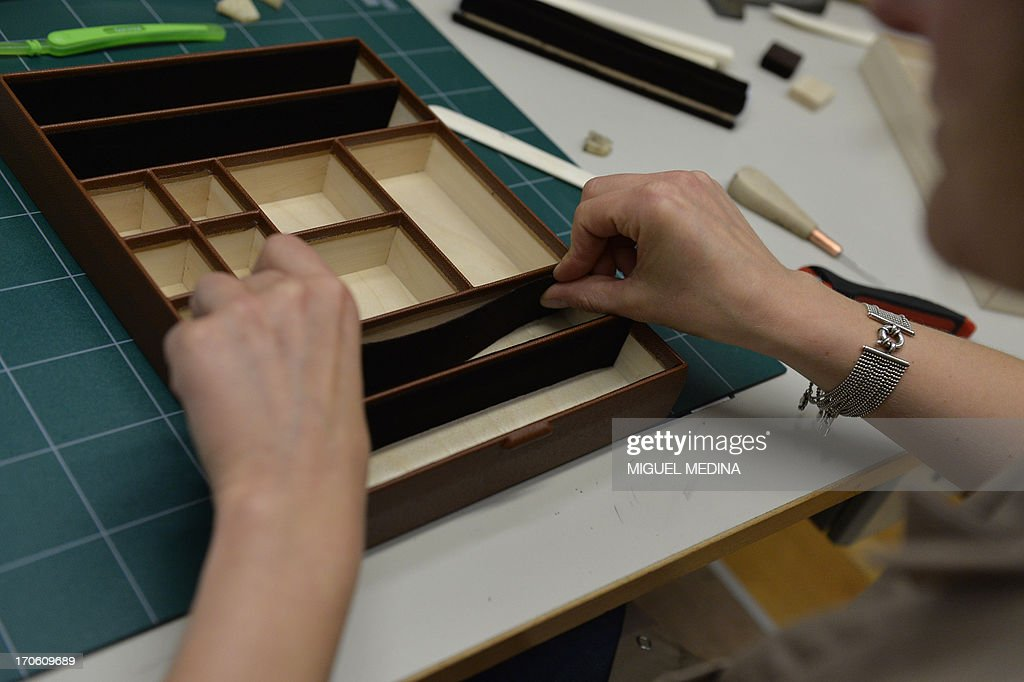 A craftswoman applies a piece of leather to the compartment of a trunk at the bag workshop of luxury brand Louis Vuitton, part of France-based luxury goods company LVMH Moet Hennessy Louis Vuitton SA, in Asnieres-sur-Seine near Paris on June 15, 2013.