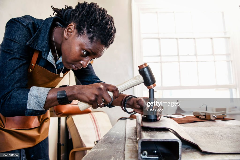 Craftswoman at work, making leather goods for her small business. : Stock Photo