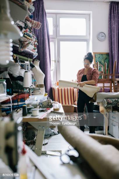 Craftswoman Deciding On Material For Next Upholstery Project