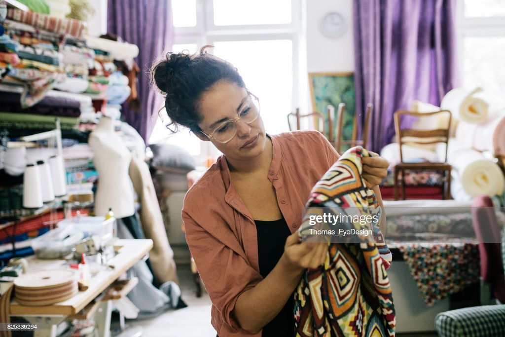 Craftswoman Examining Colorful Fabric In Workshop : Stock Photo
