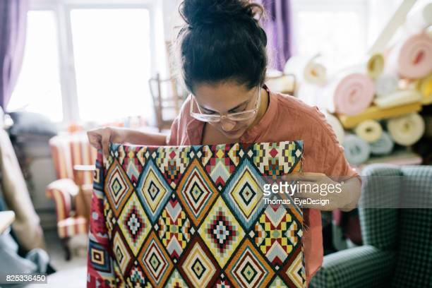 Craftswoman Examining Colourful Sheet Of Fabric