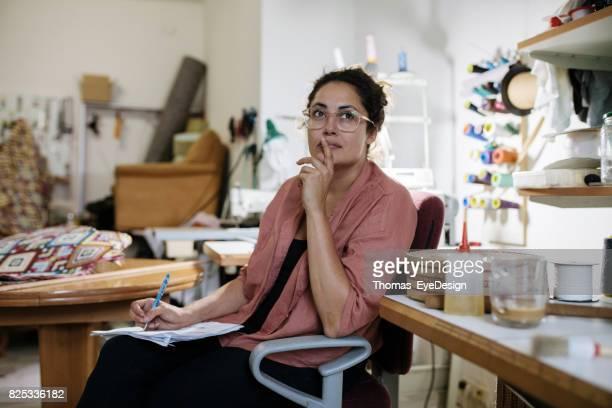 Handwerkerin, die auf der Suche nach Inspiration im Hause Polsterei