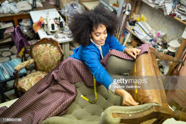 craftswoman measuring old armchair for making reupholstery, high angle view - restoring stock pictures, royalty-free photos & images