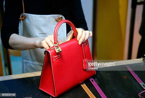 A craftswoman of the luxury brand Hermes works on a leather handbag named 'Kelly' during the 'Hermes hors les murs' event on November 23 2016 in...