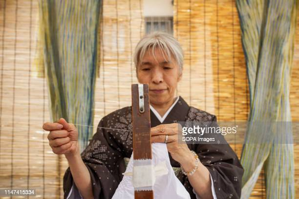 ARIMATSU NAGOYA AICHI JAPAN A craftswoman sewing a piece of cloth during the Arimatsu Shibori Festival Thirty young successors showed the 400years...