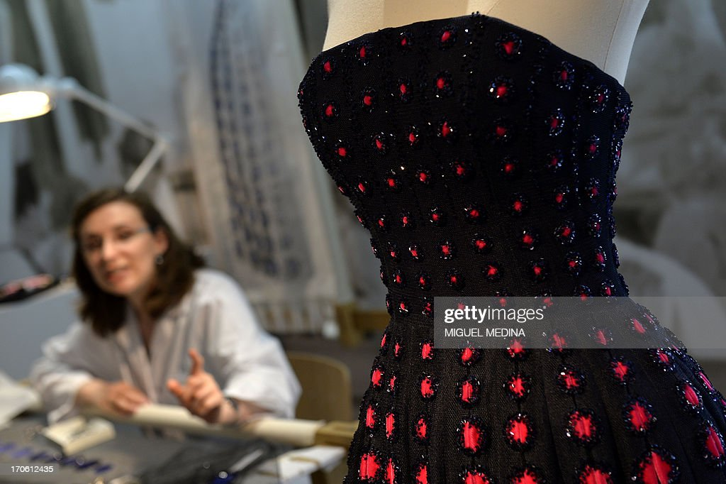A craftswoman shows a dress with embroideres at the fashion and accessories workshop of French luxury brand Dior in Paris on June 15, 2013.