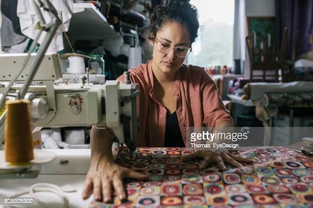 Craftswoman Using Sewing Machine In Workshop